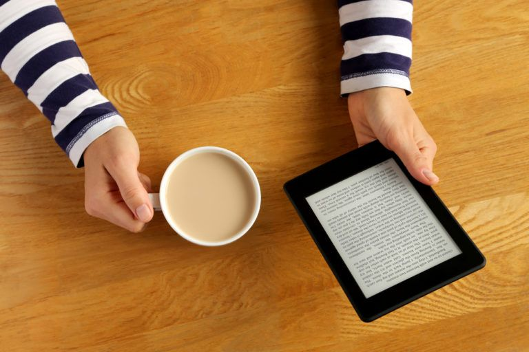 A pair of hands holding a cup of coffee and a Kindle
