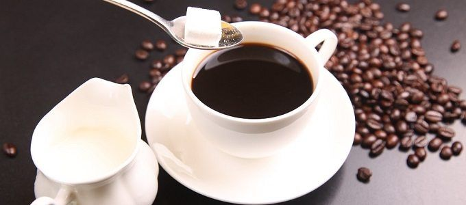 cup of coffee with sugar cube, cream and coffee beans