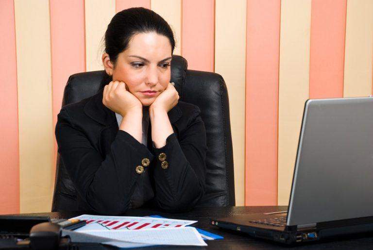 Woman sitting at her desk looking worried as an example of jobs for people with anxiety