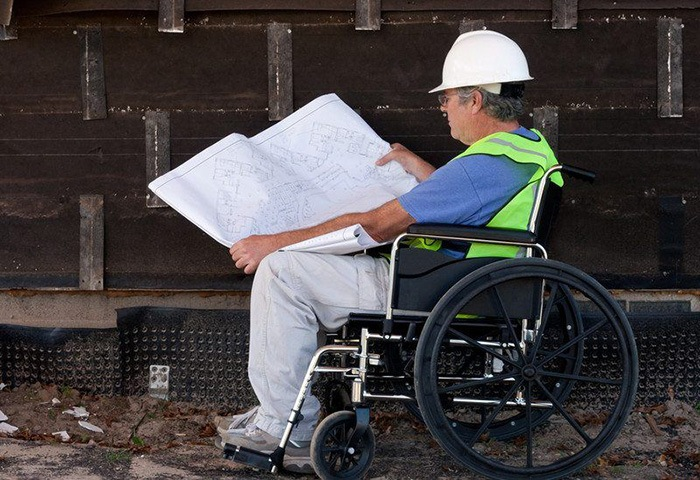 Man in a wheelchair reading blueprints as an example of jobs for people with disabilities