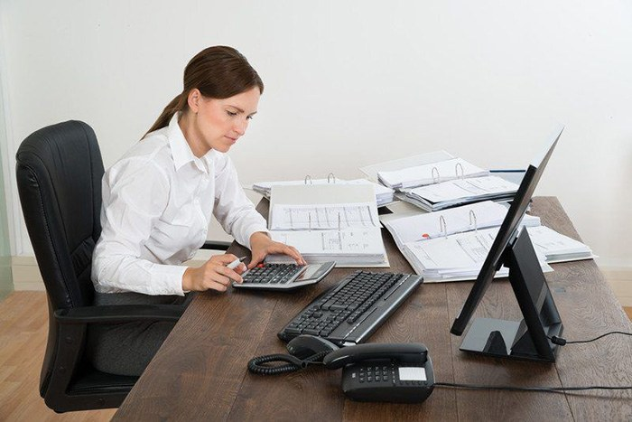 Woman busily working at her desk adding numbers on a calculator as an example of jobs for people with Asperger's