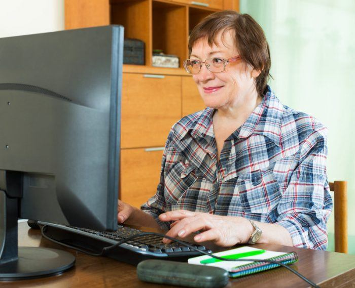 Older woman working at a computer station as an example of jobs for retirees