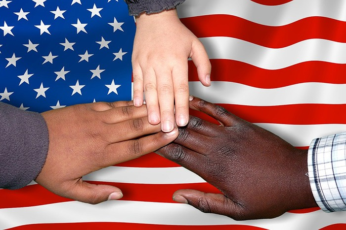 Three hands coming together over an American flag as an example of jobs for new immigrants
