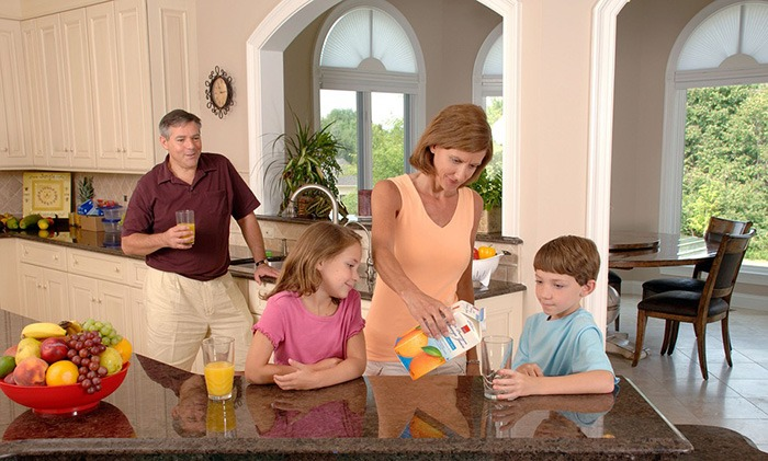 Mother pouring a glass of orange juice for her son as an example of job ideas for stay at home moms