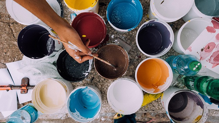 A collage of buckets of paint containing different colors as an example of jobs for artists
