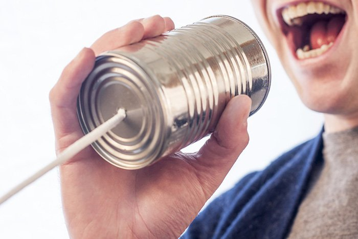 Man speaking into a tin can toy as an example of jobs for communications majors