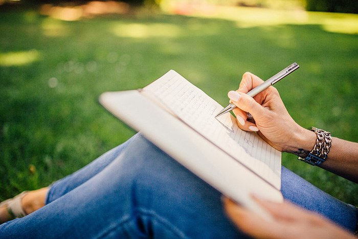 Woman sitting in the grass writing in a notebook as an example of jobs for online writers