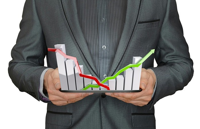 Man in a suit holding a bar graph in both hands representing economic data