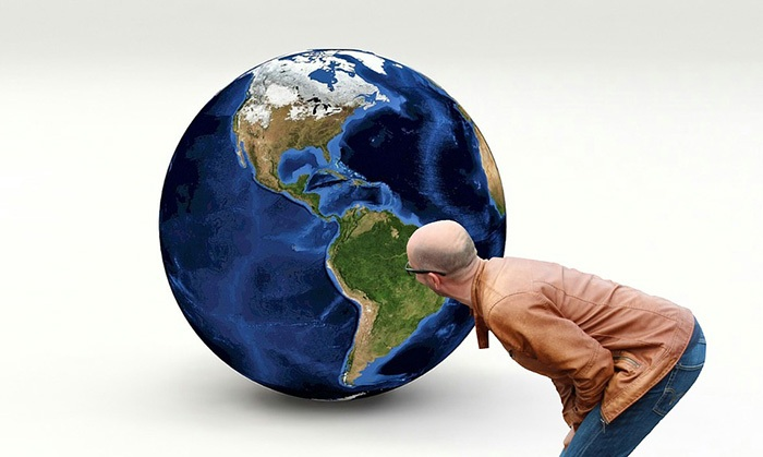 Man in leather coat staring at a large globe on the floor as an example of jobs for geography majors