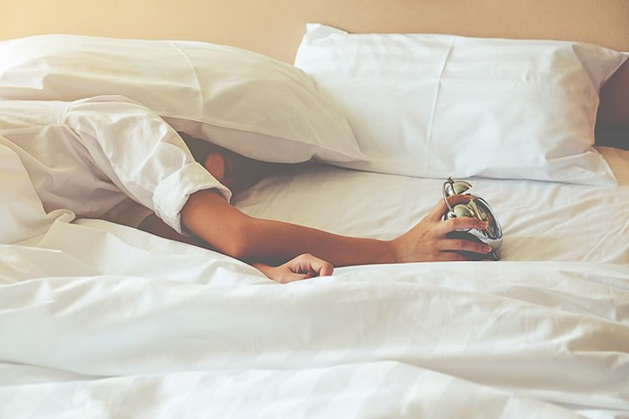 Woman in bed under the covers with her hand turning off an alarm clock as an example of jobs for lazy people