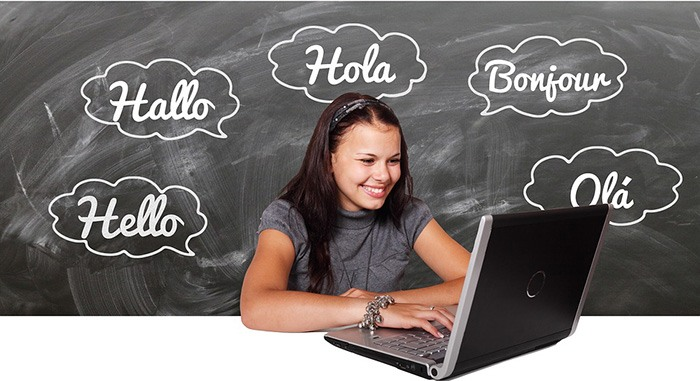 Young student on her laptop with a cloud of  words in different languages written on a chalkboard as an example of a linguistics major