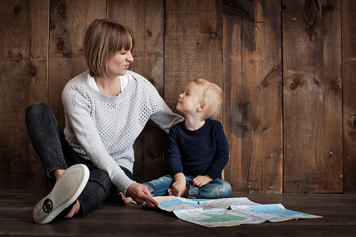 Young mom sitting on the floor with her child looking lovingly into his eyes as an example of jobs for nurses who are moms
