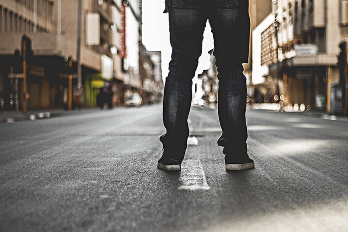 Man standing alone on an empty street as an example of jobs for loners.