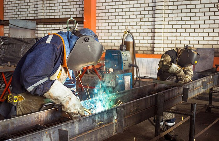 Man working in a shop welding a steal beam as an example of best jobs for welders