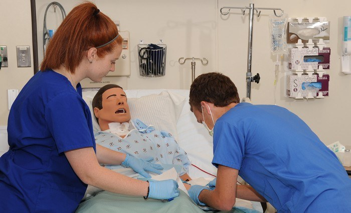 Two nursing students practicing their skills on a dummy in a patient bed as an example of jobs for nursing students
