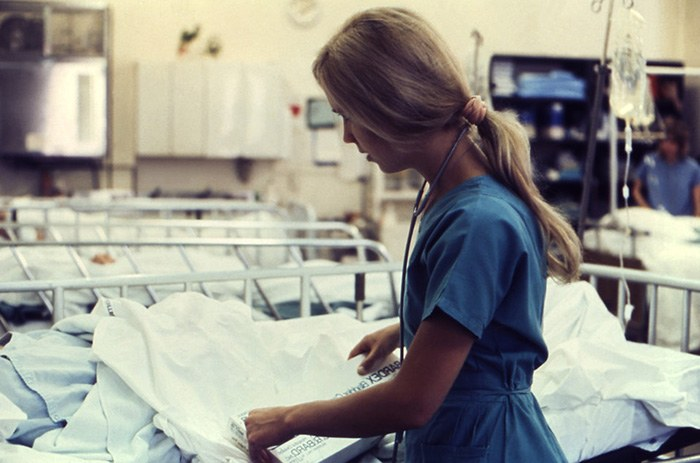 Picture of a woman working as a nurse changing the linen on a patients bed as an example of moonlighting jobs for nurses