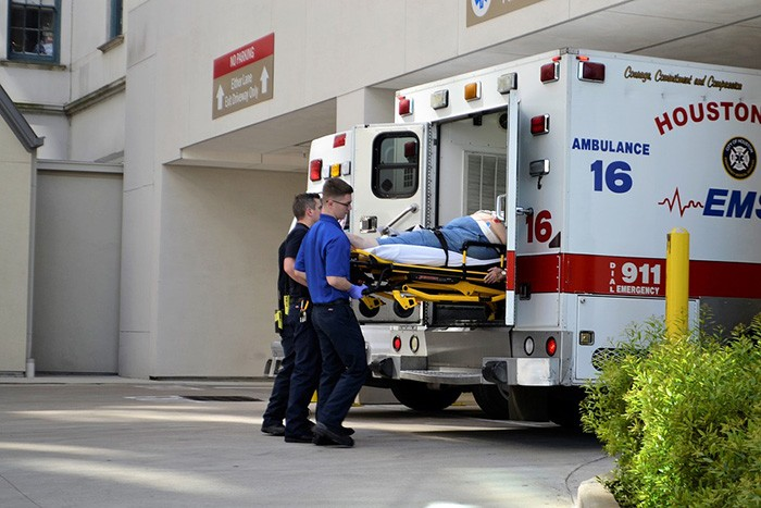 Two men working as paramedics loading a patient into an ambulance as an example of ESFP personalities