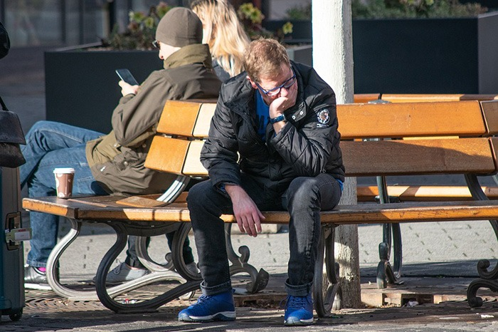 Man sitting on a park bench in distress representing an antisocial person