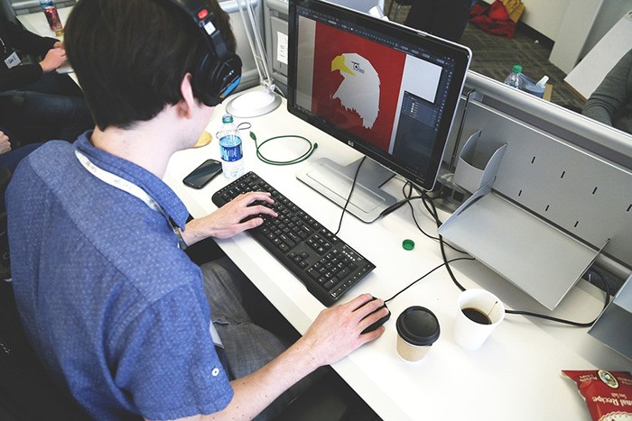 Younger man sitting at a computer drawing an object with his mouse as an example of a graphic designer