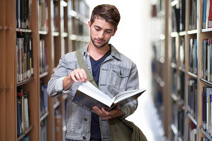 Younger man reading a book in a college library as an example of an undergraduate student