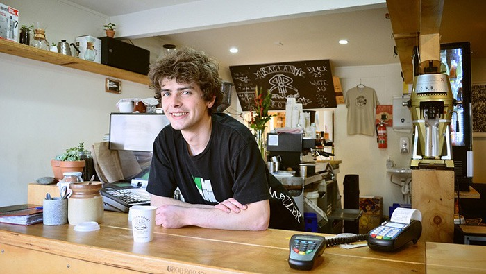 Young man smiling working the counter at a coffee shop representing a job for younger people