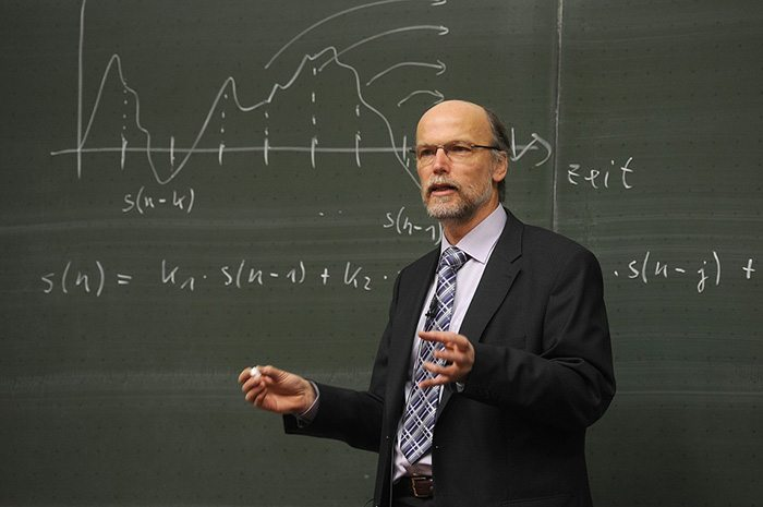 Teacher standing in front of a chalkboard lecturing a class as an example of a retired teacher returning to the workforce