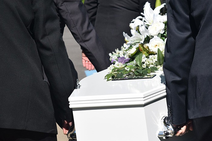 Photo of men carrying a coffin at a funeral as an example of getting a job writing obituaries