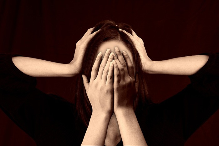 Photo of a woman with her hands over here head as an example of getting paid to write about mental illness