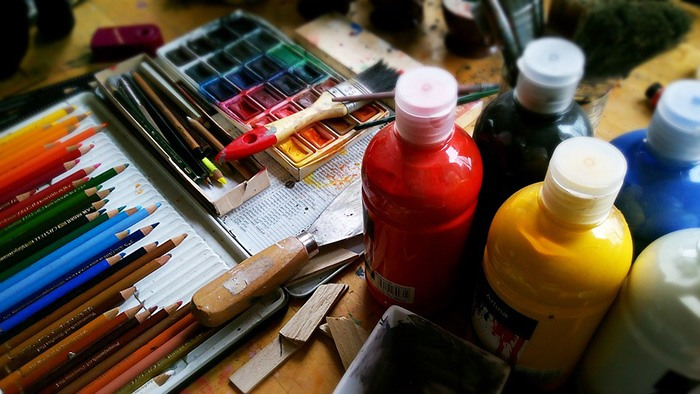 Photo of a cluttered table of art supplies as an example of getting paid to write about art