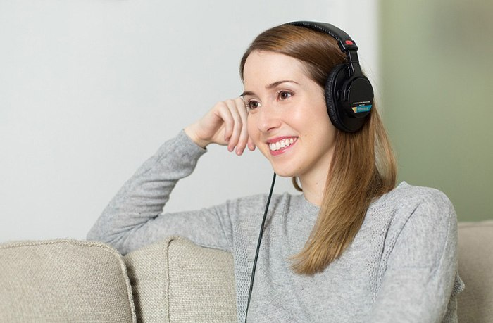 Young woman listening to a pair of headphones as an example of getting paid to write about music