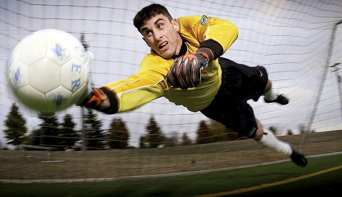 Photo of a soccer goalie diving for a ball as an example of writing about sports