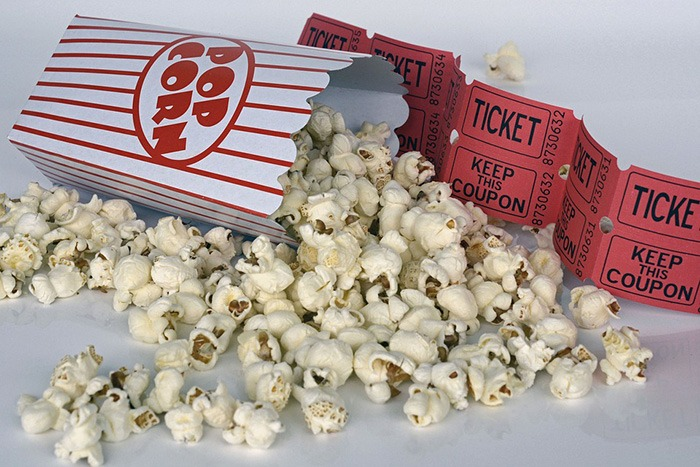 Photo of popcorn and movie tickets as an example of movie reviews