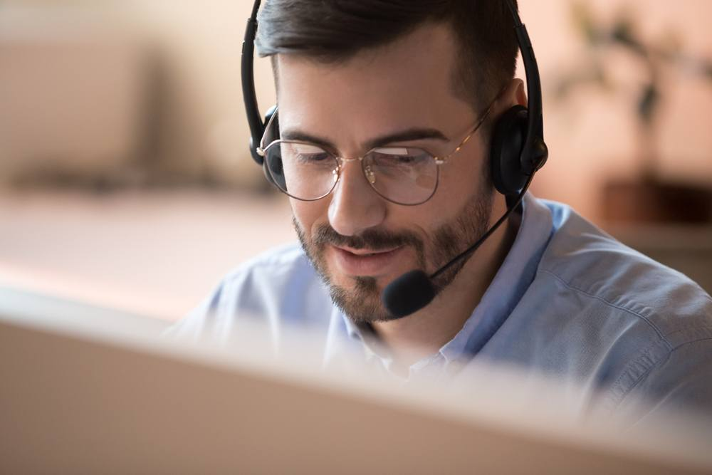 A man sitting on his computer wearing a headset being a telemarketer