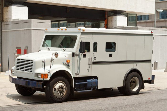 Picture of an armored car delivering money in front of a large building probably a hotel or bank