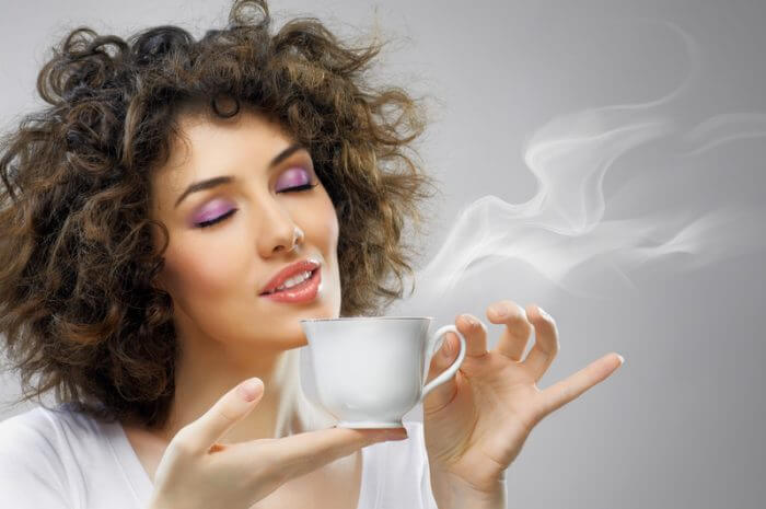 Young woman holding a cup of coffee with her eyes closed.