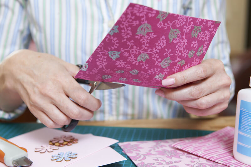 Image of a woman scrapbooking at a home.