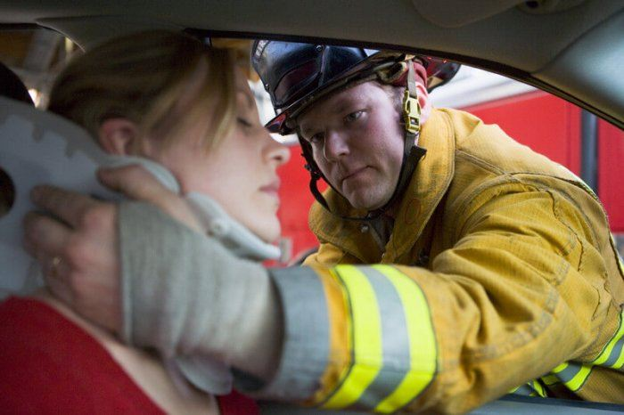Firefighter helping a women with an injured neck in the car