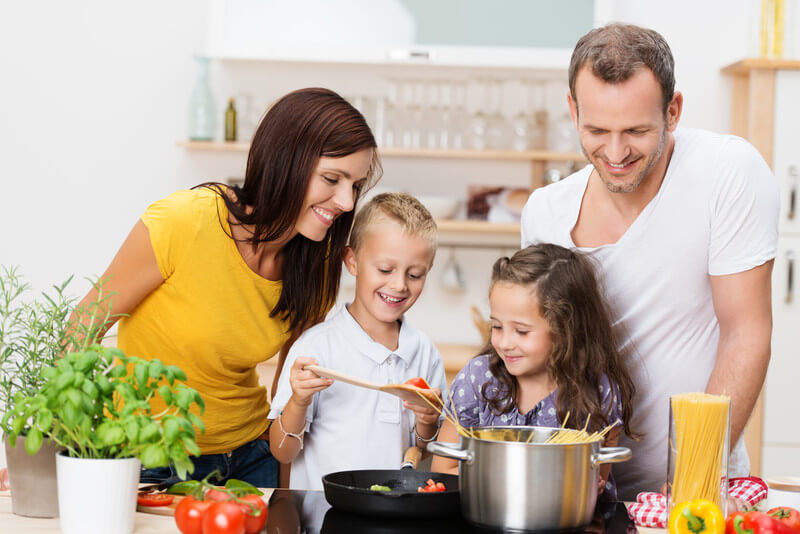 Young family in a kitchen preparing dinner.