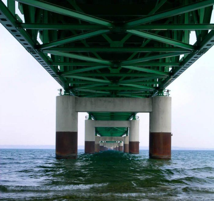 Picture of a thick metal green, red, and white bridge over a body of dark blue water. This is a potential site where and underwater welder might be needed
