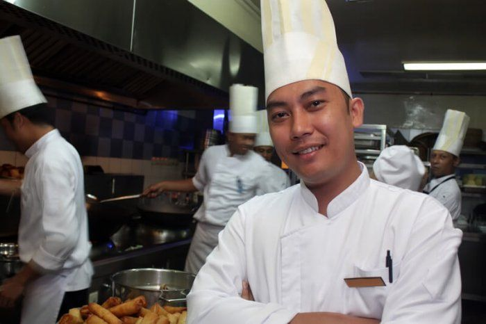 asian chef standing in a kitchen with several assistant chefs in the background doing work