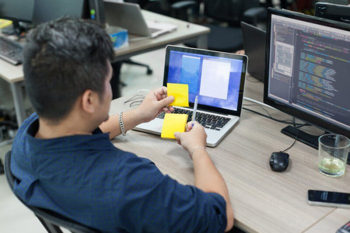 a man with dark hair sitting at an office desk doing we development and looking at two sticky notes in his hand