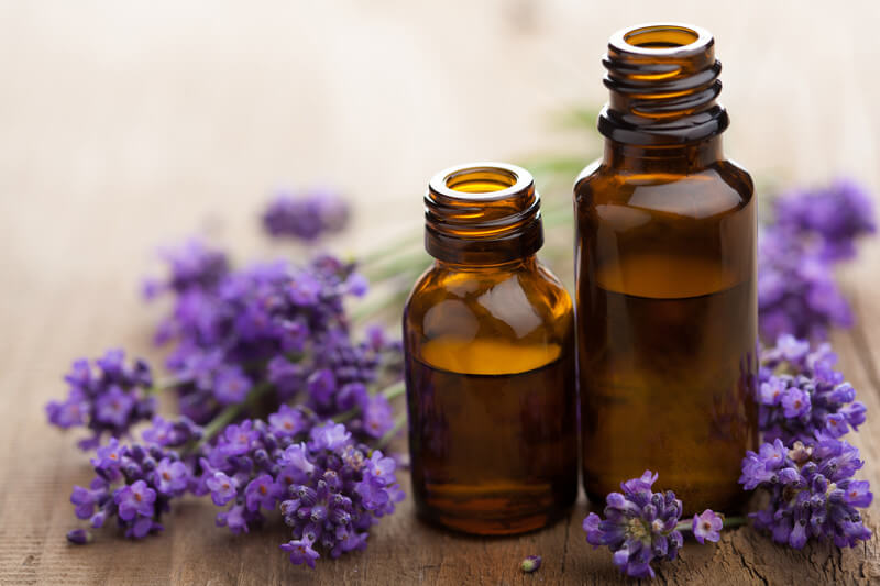 Image of two open bottles of essential oils with various lavender flowers next to them