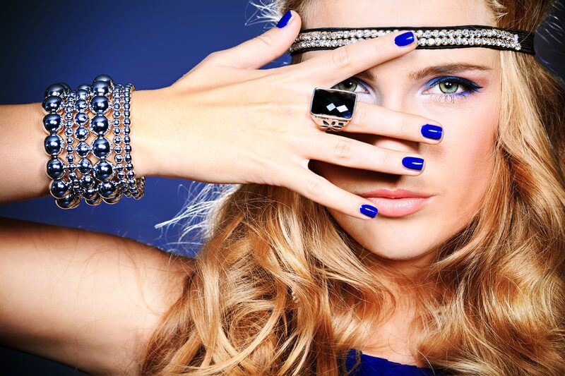 Image of a blonde woman wearing blue with various pieces of jewelry.