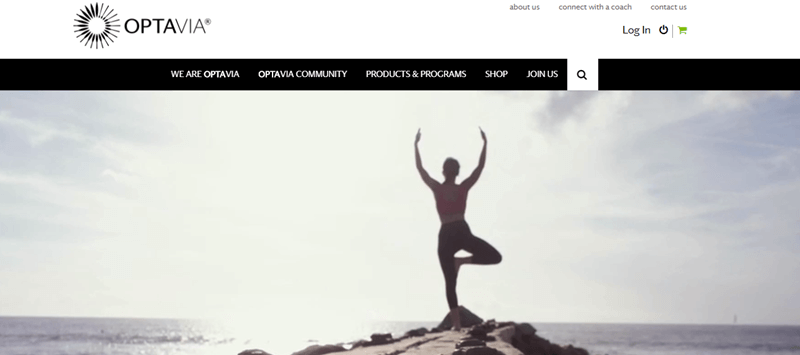Optavia website screenshot showing an image of a young woman outside in front of the sea doing a yoga tree pose.