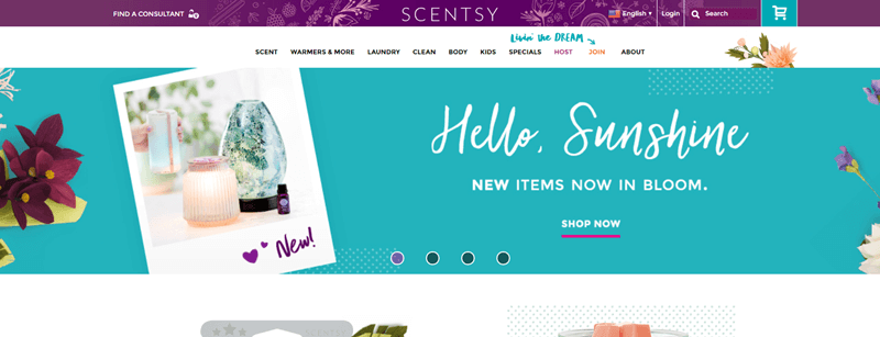 Scentsy website screenshot showing a blue banner with the words 'Hello, Sunshine', A diffuser and candle are also highlighted, along with various flowers.