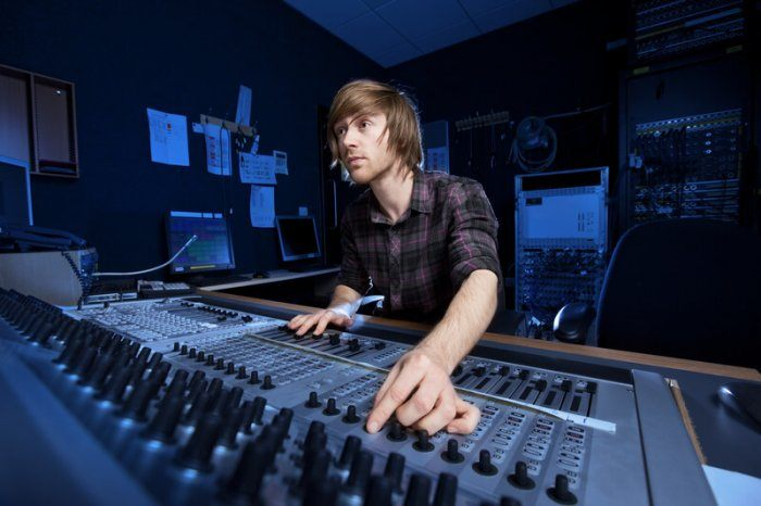 sound technician tweaking a knob and looking intensely