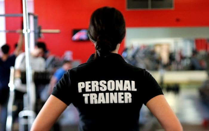 """young woman in black shirt with print that says, """"Personal Trainer"""""""