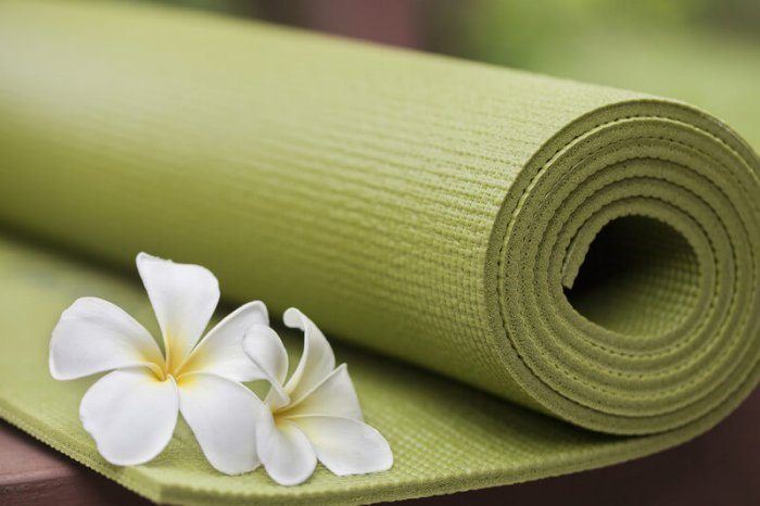 green yoga mat with white flower representing the best yoga affiliate programs