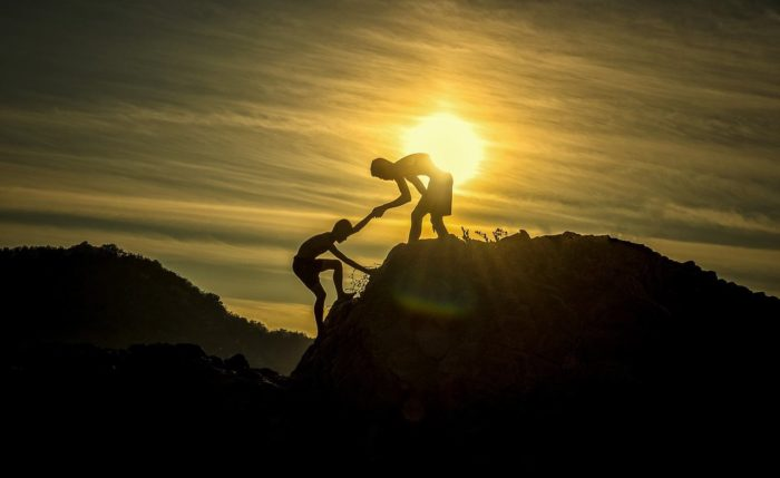 friends helping each other climb a mountain