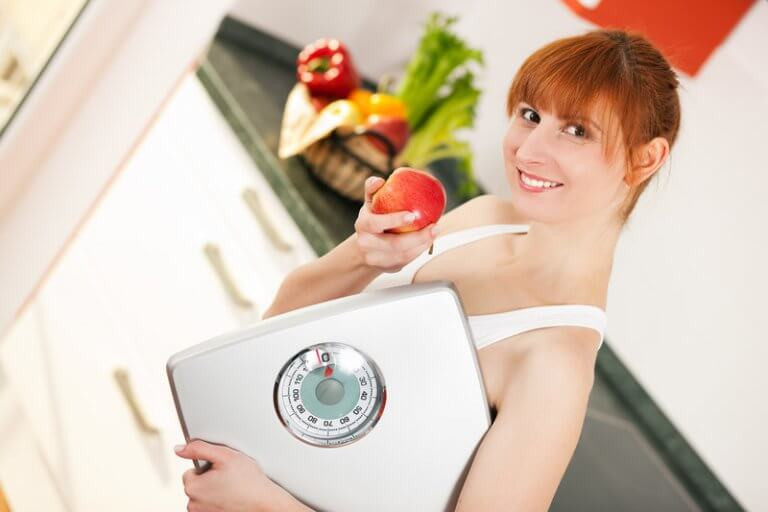 Weight loss concept image showing a red haired woman with a scale.